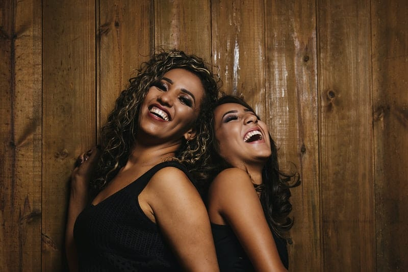 Zwei lächelnde schwarze Frauen stehen Rücken an Rücken