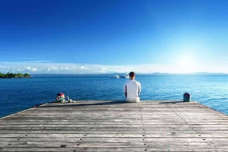 ein Mann, der alleine auf einem Seepier sitzt