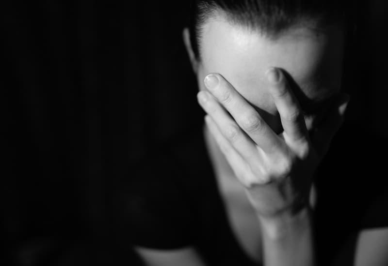 ein Schwarzweiss-Foto einer traurigen Frau mit einer Hand auf ihrem Gesicht