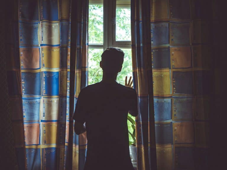ein junger Mann, der aus dem Fenster schaut