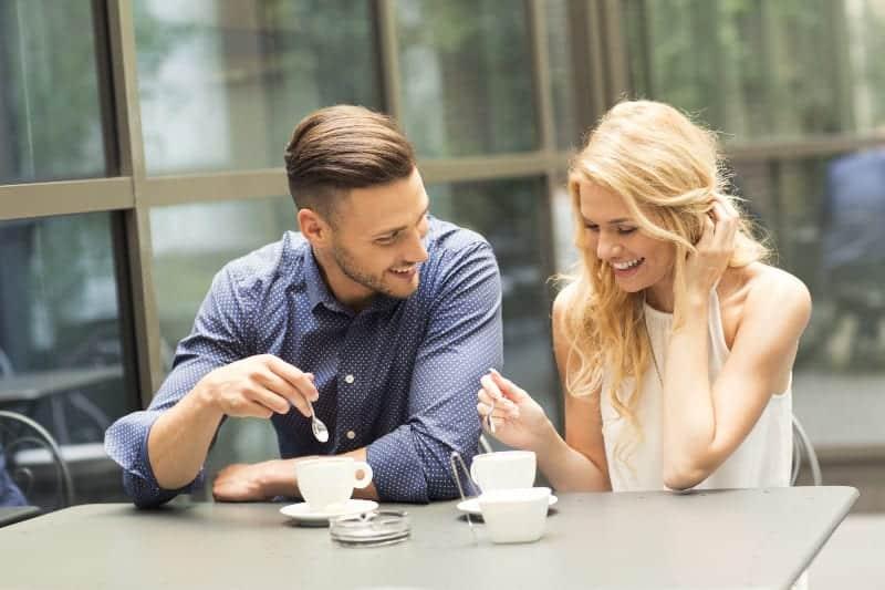 ein lächelndes Paar trinkt Kaffee auf der Caféterrasse