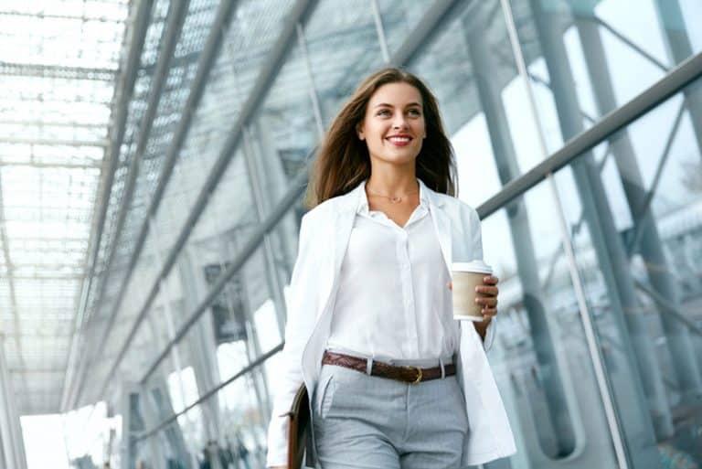 ein lächelndes junges Mädchen, das Kaffee in ihrer Hand hält