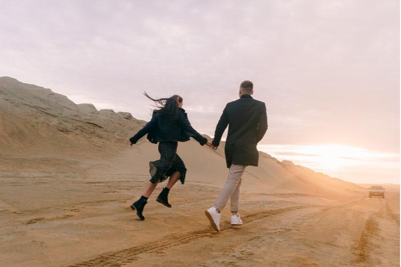 ein liebendes Paar, das in der Wüste spazieren geht