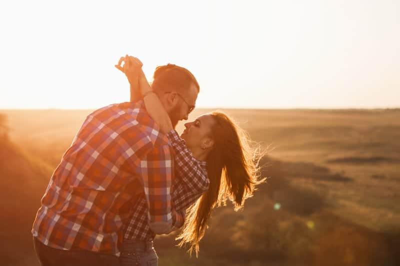ein liebendes Paar in einer Umarmung auf einem Hügel