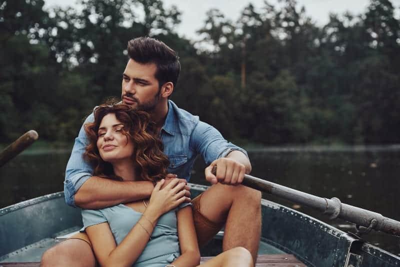 eine Frau, die in den Armen eines Mannes in einem Boot sitzt