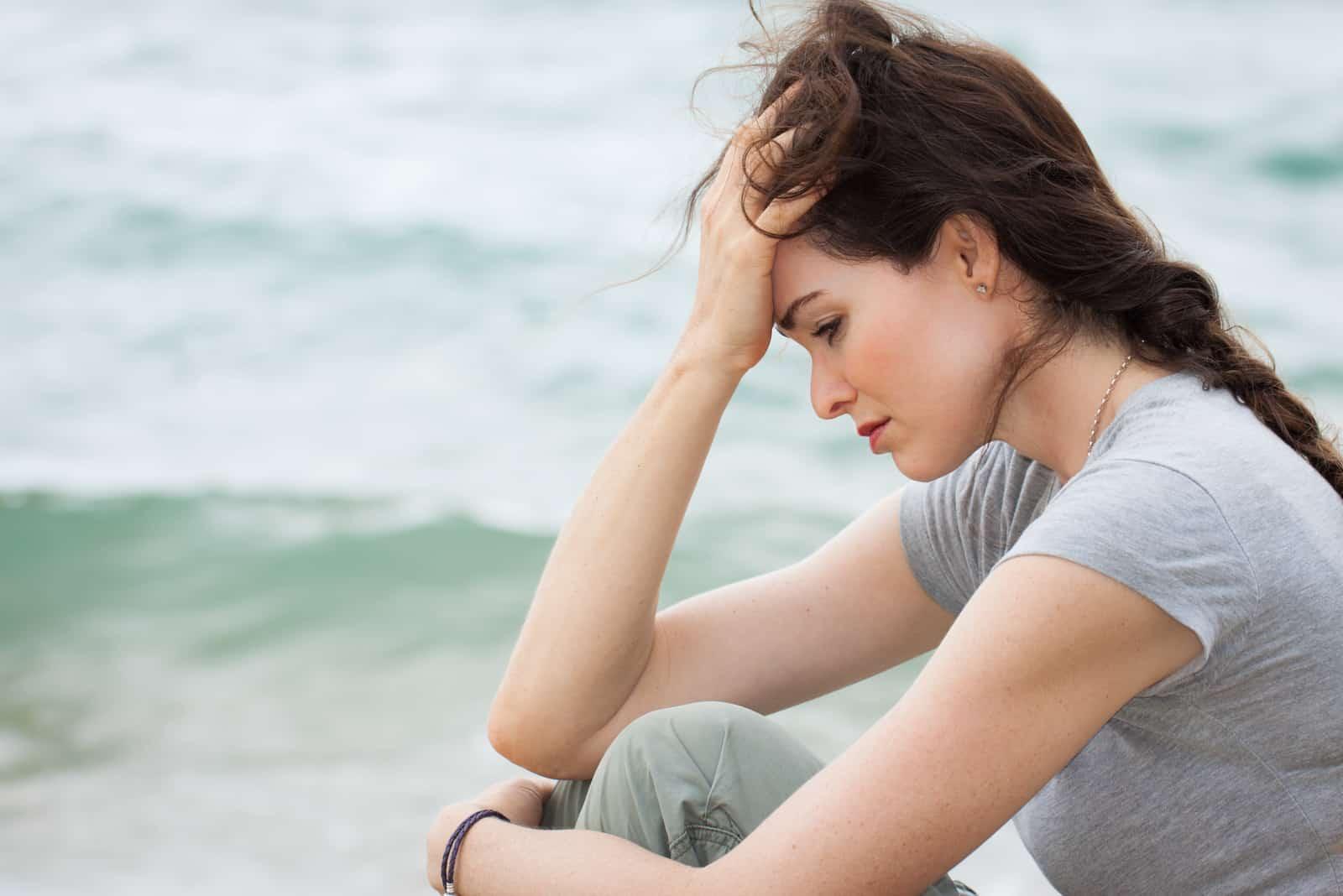 eine depressive Brünette sitzt am Meer