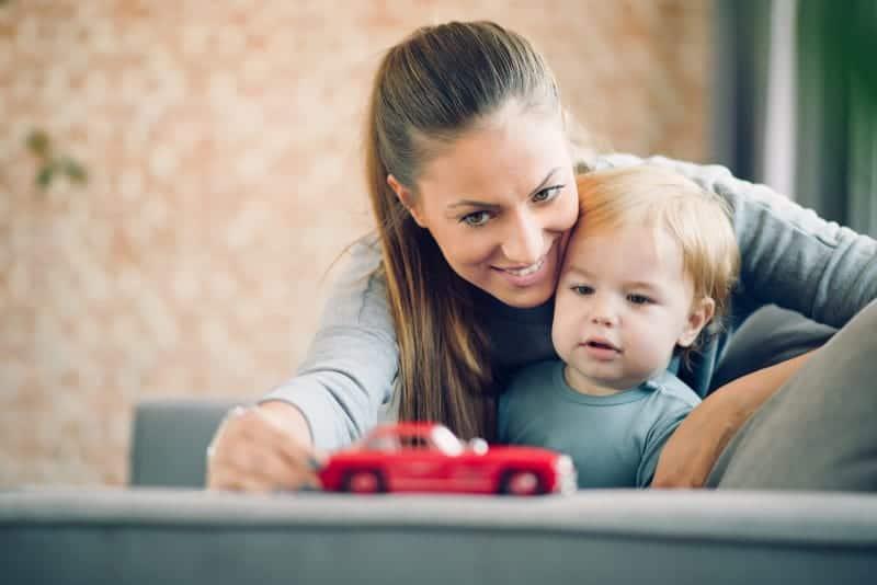 eine lächelnde Mutter spielt mit ihrem Sohn