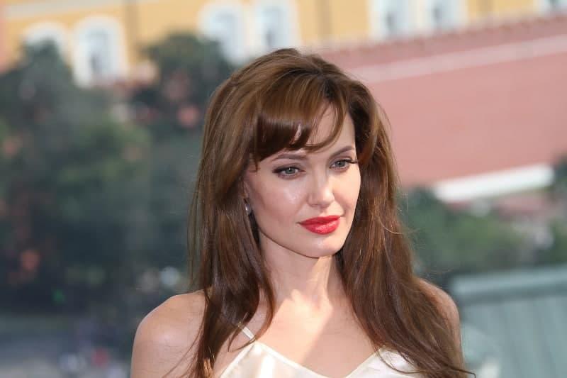eine nachdenkliche Frau mit rotem Lippenstift