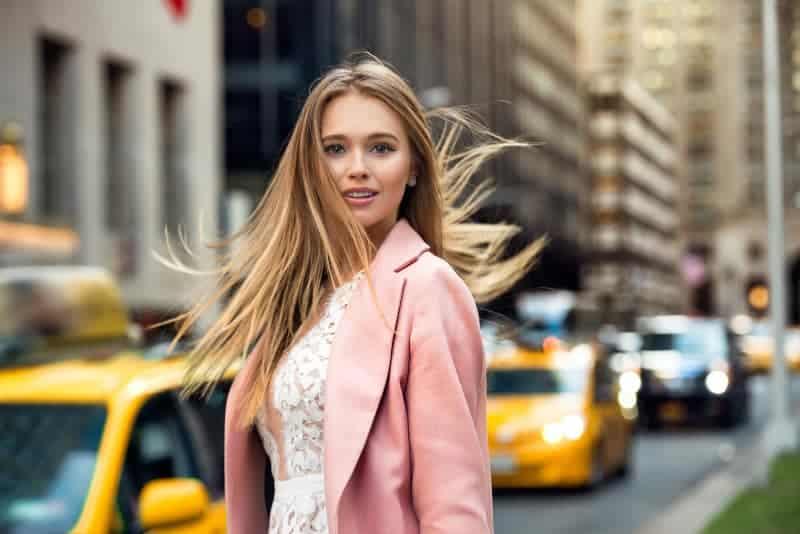 junge blonde Frau, die auf Straße steht
