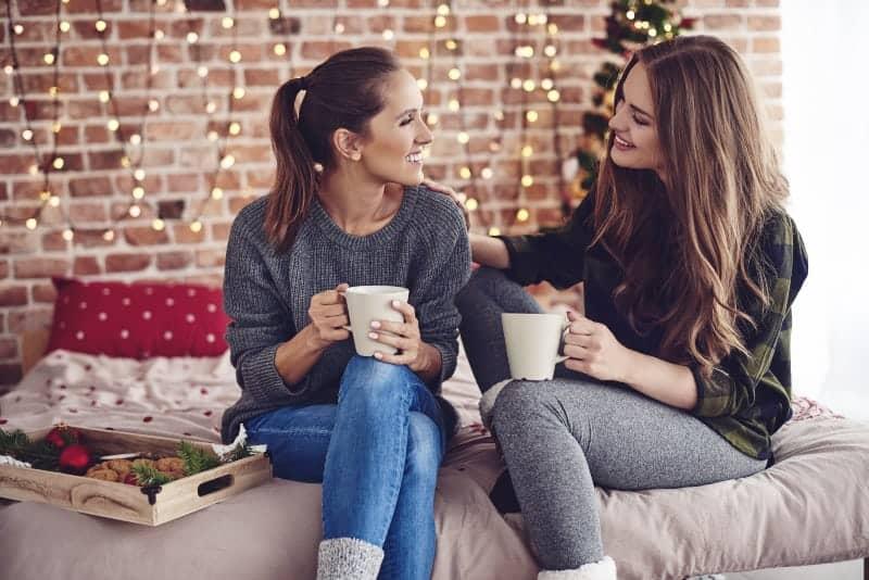 lächelnde Freunde sitzen auf dem Bett und unterhalten sich bei einem heißen Getränk