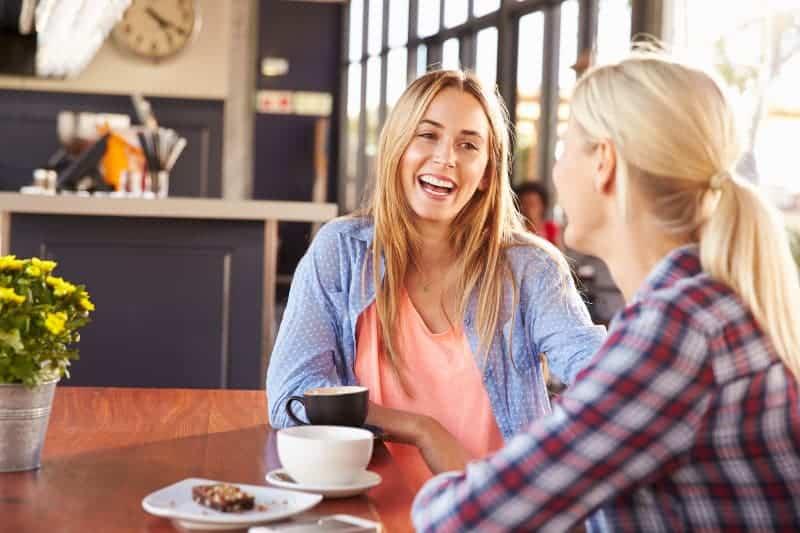 lächelnde Mädchen sitzen in der Küche und trinken Kaffee