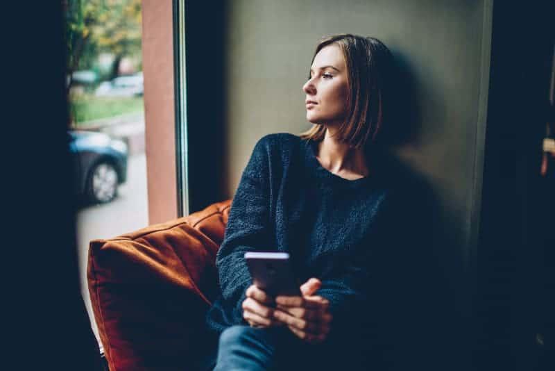 nachdenkliche Frau mit Handy in der Hand, die aus dem Fenster schaut