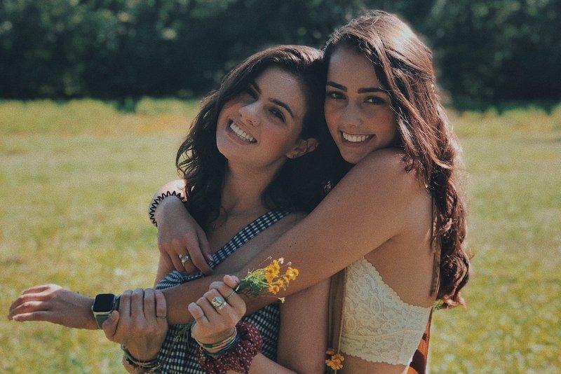 zwei Freunde auf einem Feld stehen in einer Umarmung