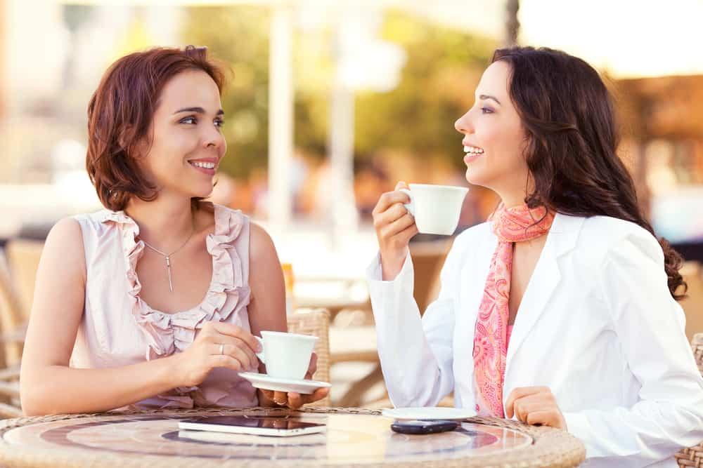 zwei lächelnde Freunde, die Kaffee trinken