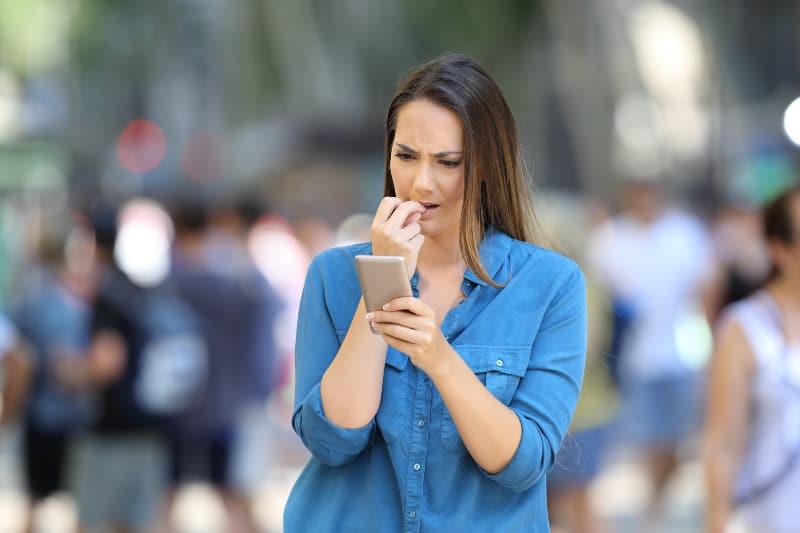 ängstliches Mädchen in der Stadt, das besorgt auf ihr Handy schaut