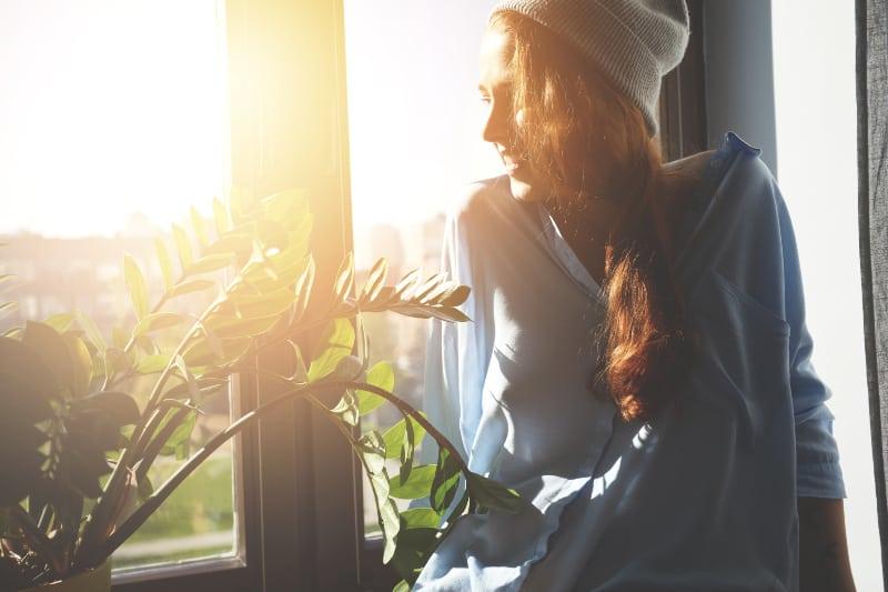 Das Mädchen in der Sonne schaut aus dem Fenster