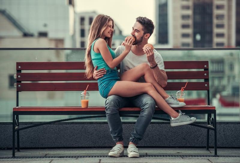 Das Mädchen sitzt auf dem Mann in ihrem Schoß