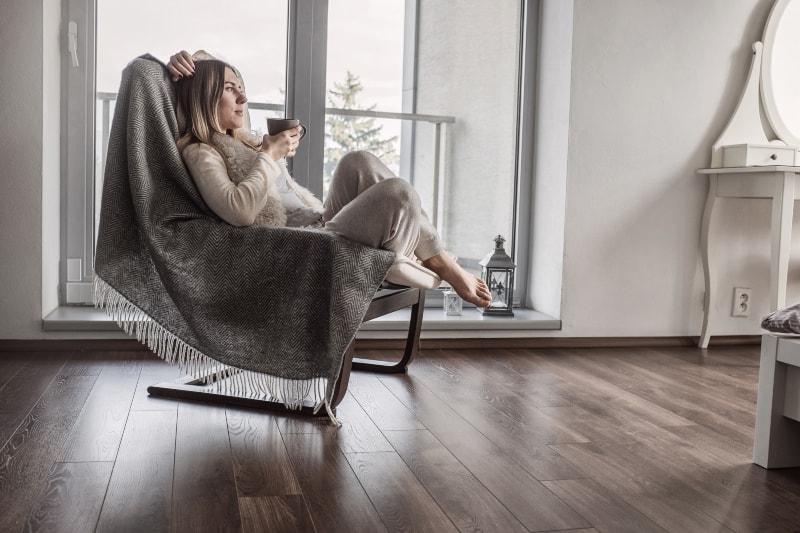 Das Mädchen sitzt auf einem Sessel und trinkt Kaffee
