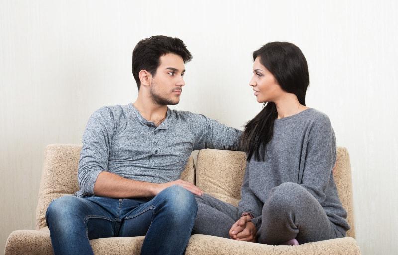 Das Paar sitzt auf der Couch und redet