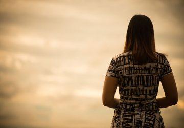 traurige junge Frau im Sonnenuntergang am Wasser