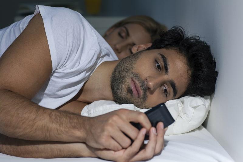 Der Mann behält sein Handy, während seine Freundin schläft