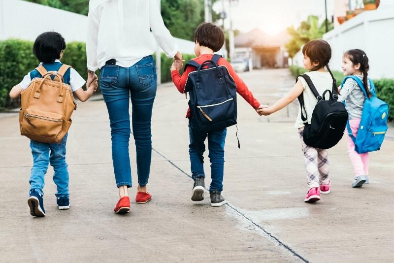 Die Mutter bringt die Kinder zur Schule