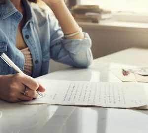 junge Frau schreibt einen Brief an ihre Mutter