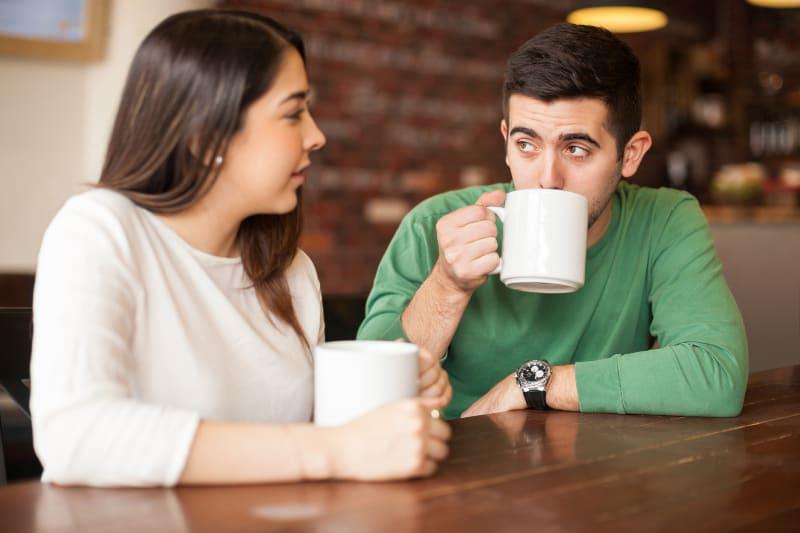 Ein Mann hört einem Mädchen zu, während er spricht und Tee trinkt