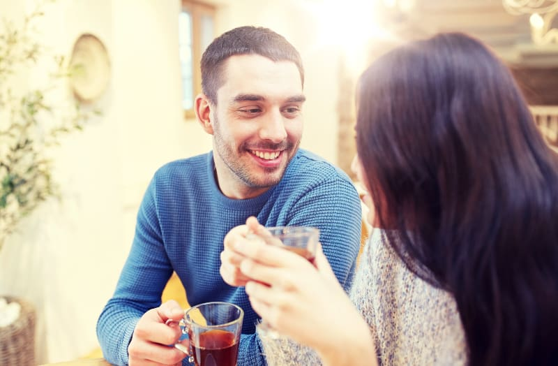 Ein Mann in einem blauen Pullover trinkt mit einer Frau Tee