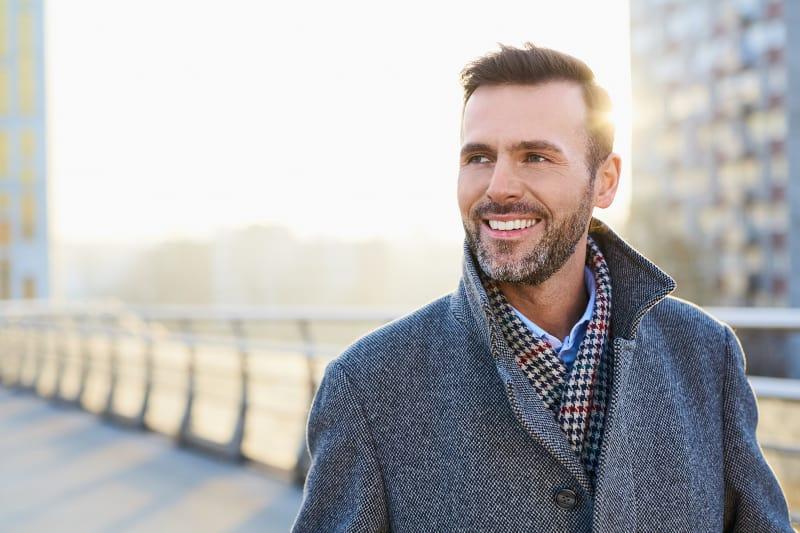 Ein lächelnder Mann geht durch die Stadt