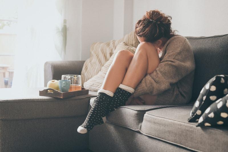 Ein trauriges Mädchen im Wohnzimmer sitzt auf der Couch