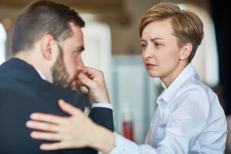 Eine Frau mit kurzen Haaren tröstet ihre traurige Kollegin