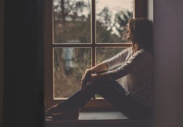 traurige junge Frau, die am Fenster sitzt