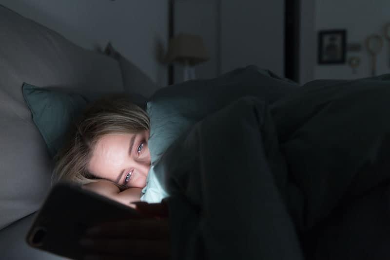 traurige Frau am Telefon im Bett von einer Decke bedeckt