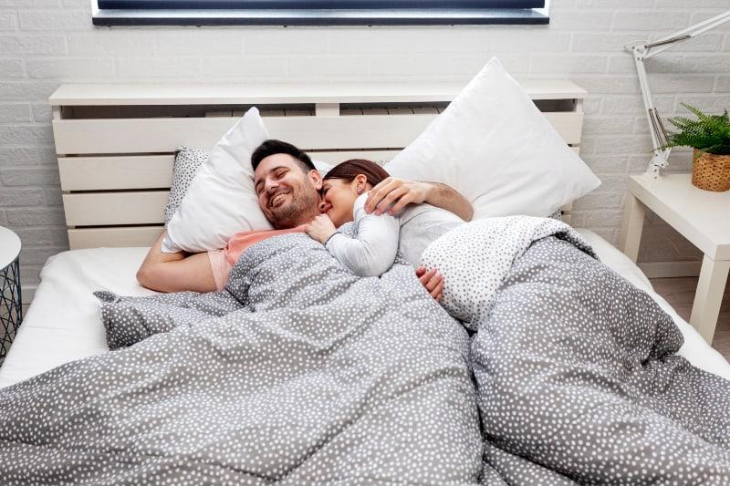 Paar im Bett umarmt