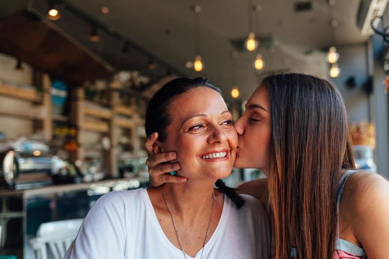 Frau küsst ihre Mutter lächelnd an der Bar