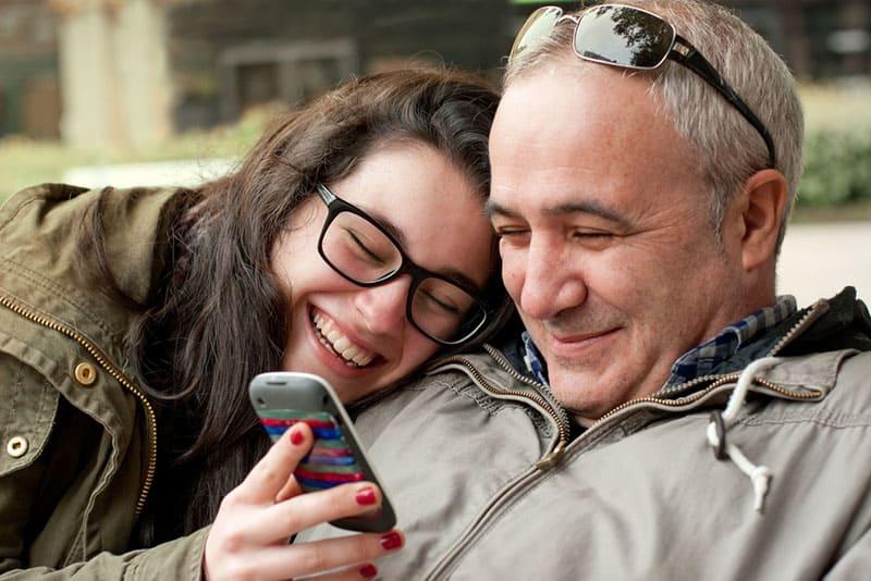 Tochter und Vater lachen über ein lustiges Video am Telefon