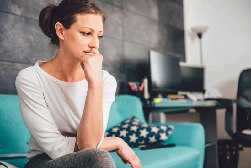 Traurige Frau, die auf einem Sofa sitzt