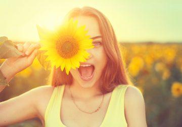 Porträt einer schönen glücklichen Frau, die eine Sonnenblume hält
