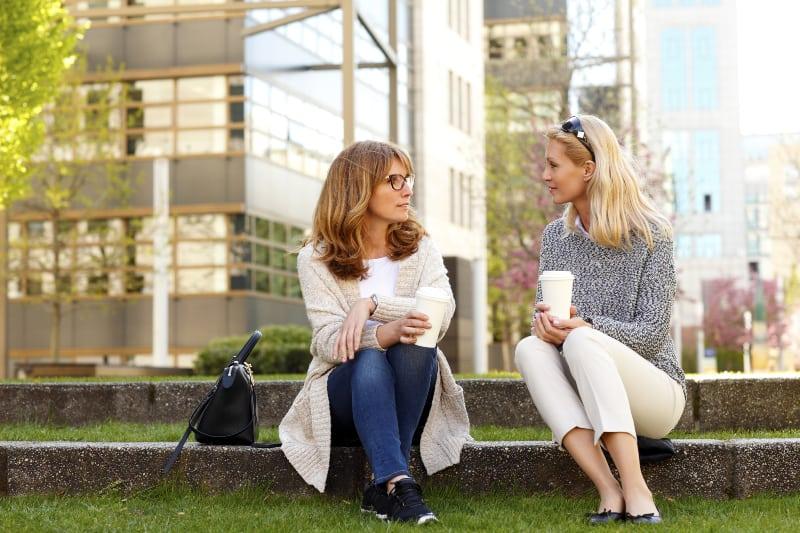 Zwei ältere Damen sitzen vor einem Gebäude auf dem Rasen