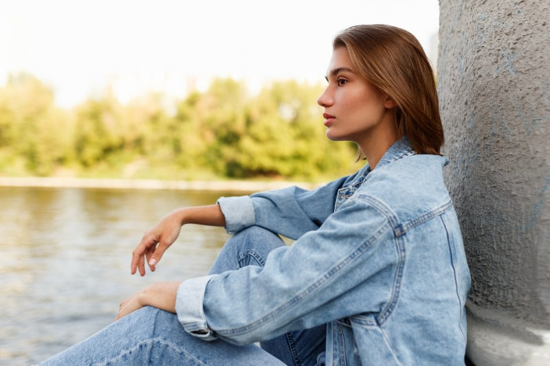 attraktive Frau, die nahe See sitzt