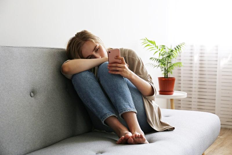 depressives Mädchen sitzt auf der Couch und schaut auf Handy