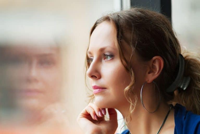ein Mädchen, das am Fenster sitzt und den Regen fallen sieht