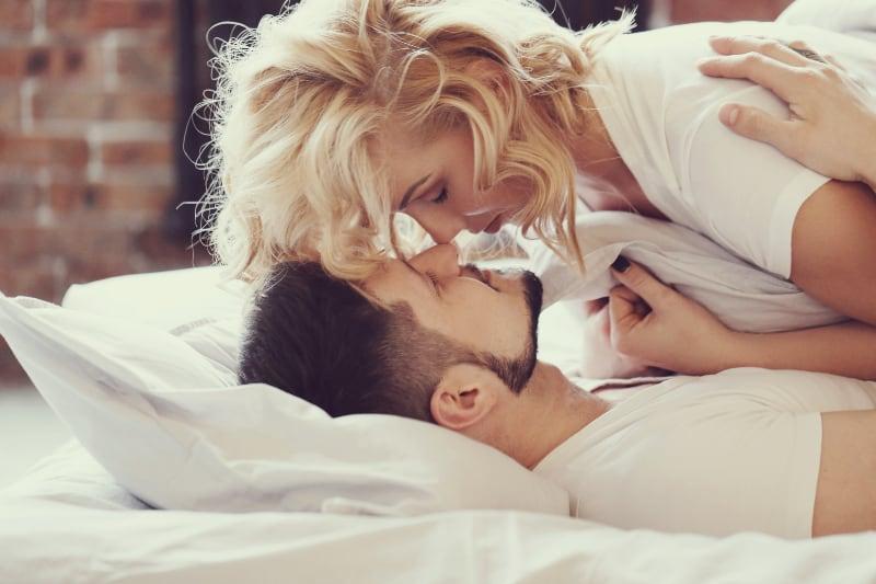 ein Mädchen, das ihren Freund im Bett küsst