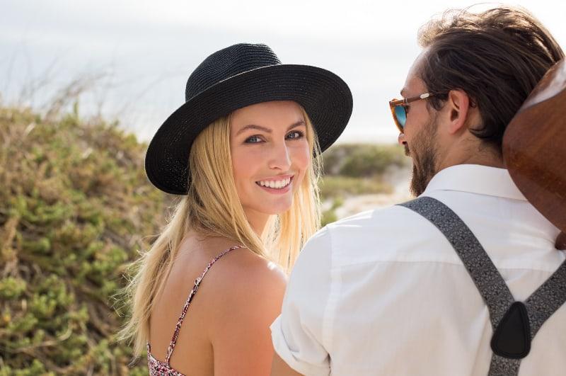 eine junge attraktive Blondine mit Hut und ihrem Freund