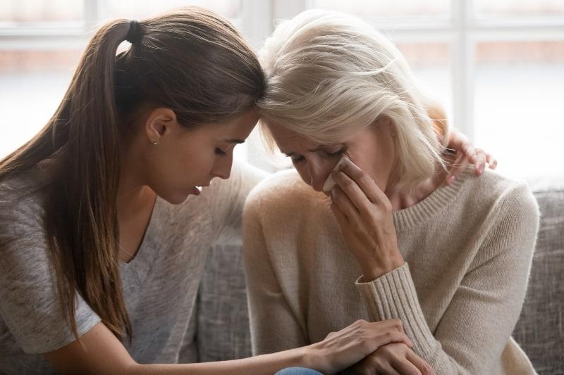 eine traurige Mutter und eine Tochter, die sie tröstet