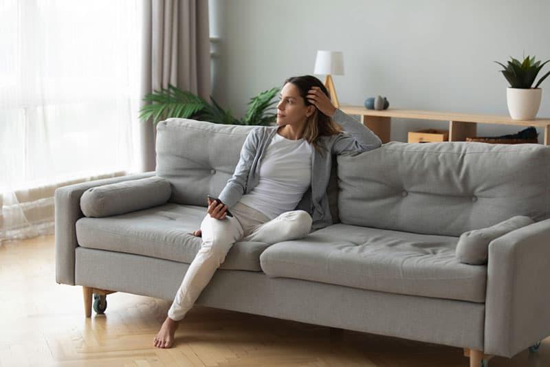 einsame ruhige fällige Frau auf dem Sofa, das mit ihrem Telefon sich entspannt