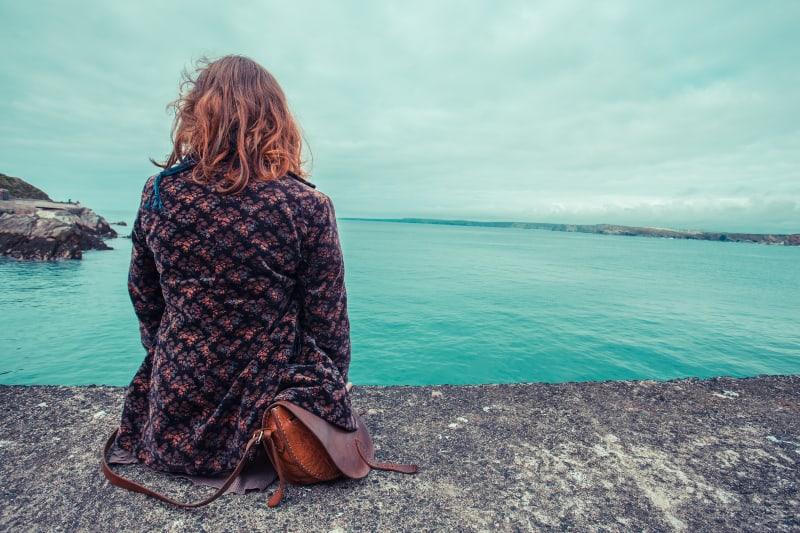 einsames Mädchen sitzt an der Wand