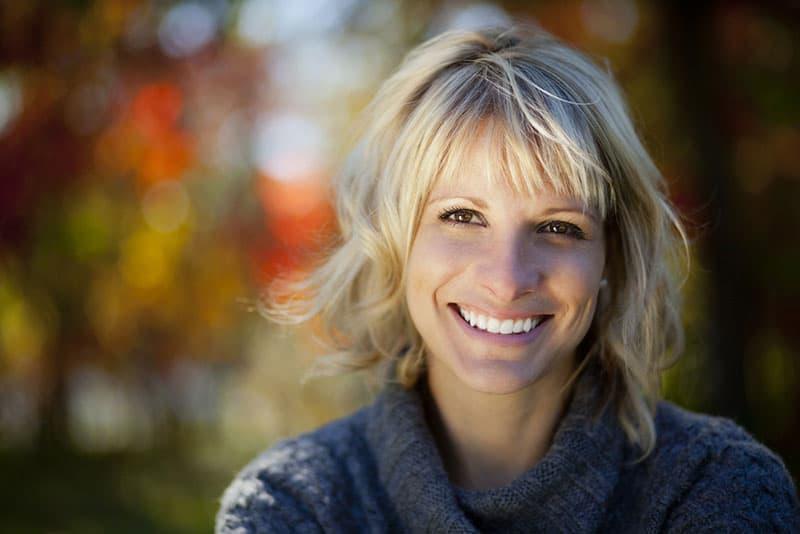 glückliche blonde Frau, die im Park lacht