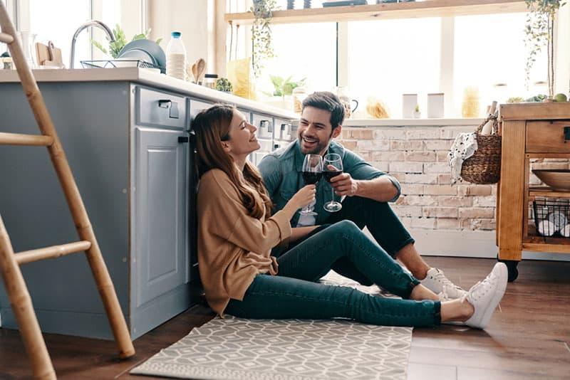 glückliches Paar lachen und sitzen auf dem Küchenboden beim Trinken von Wein